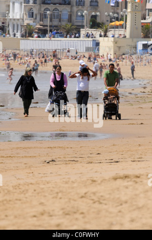 Arabic Mums with Pushchairs on beach - Stock Photo
