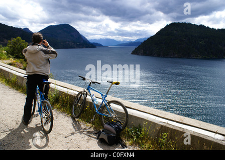 Tourist on a bicycle takes a picture of Lago Lacar near San Martin de Los Andes, Neuquen, Argentina. - Stock Photo