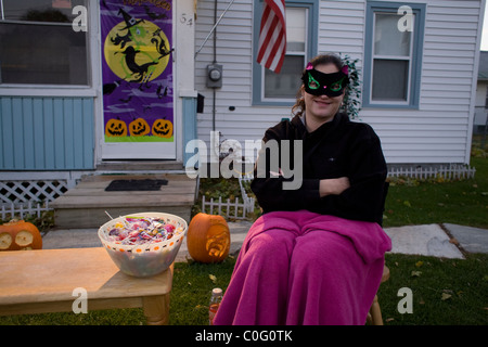 A young costumed  woman waits for trick or treaters to arrive in the late afternoon on Halloween. - Stock Photo