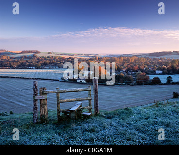 A stile on a public footpath overlooking the village of Sherrington in Wiltshire on a frosty autumn morning. - Stock Photo
