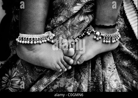 Indian babies bare feet against mothers floral sari. Monochrome - Stock Photo