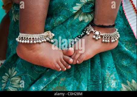 Indian babies bare feet against mothers green floral sari. Andhra Pradesh, India - Stock Photo
