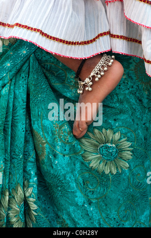 Indian babies bare foot against mothers green floral sari. Andhra Pradesh, India - Stock Photo