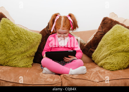 Little girl with red hair playing on the Ipad, computer tablet, whilst sitting on the sofa. - Stock Photo