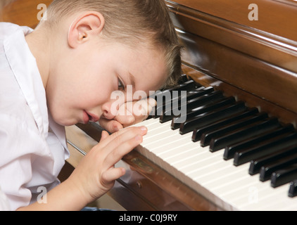 Sad Young Boy with Head on the Piano - Stock Photo