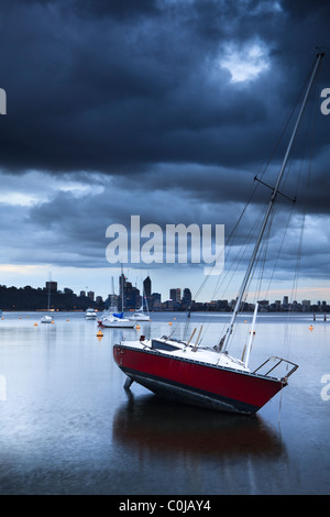 Yacht moored at Matilda Bay on the Swan River as storm clouds gather over Perth, Western Australia - Stock Photo