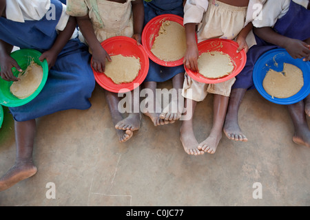 Children eat a meal at a centre for orphans and vulnerable children funded by UNICEF in Mchinzi, Malawi, Southern - Stock Photo
