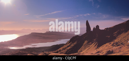 Looking South to the Cuillins. The Old Man of Storr stands alone as early morning light strikes red across the North - Stock Photo