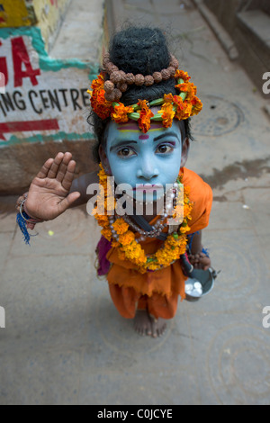 Young boy dressed as Shiva begging in the backstreets of the Old City of Varanasi, Uttar Pradesh, India - Stock Photo