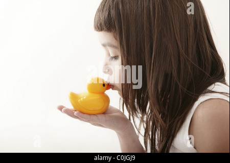 little toddler girl kissing a yellow bath duck on white background - Stock Photo