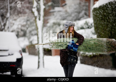 A young woman carrying a Christmas tree along a snowy street - Stock Photo