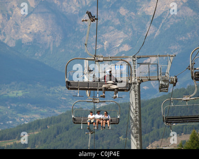 a mountainbiker plus bicycle and some wanderers going up the mountain in Les Orres, French Alps, France - Stock Photo