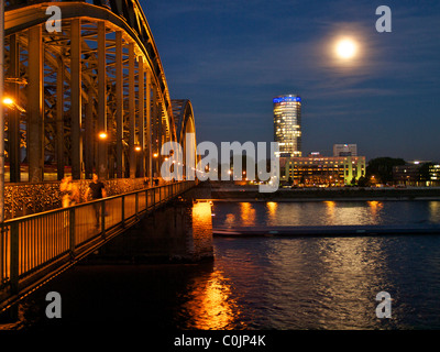 Hohenzollern railway bridge in Cologne at night, with Hyatt hotel in the background. NRW, Germany - Stock Photo