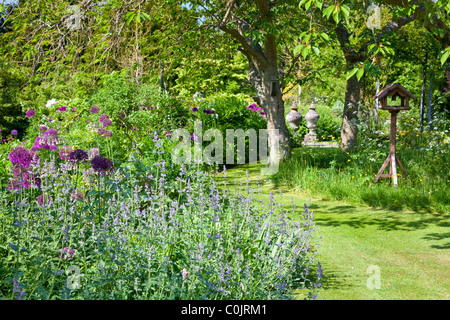 A corner of an English country garden with a grassy path leading between flower borders and a clump of shady trees - Stock Photo