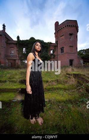 mysterious woman stood in front of an old derelict large country mansion house - Stock Photo
