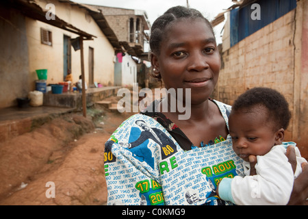 A young single mother holds her infant son outside her house in Yaounde, Cameroon, West Africa. - Stock Photo