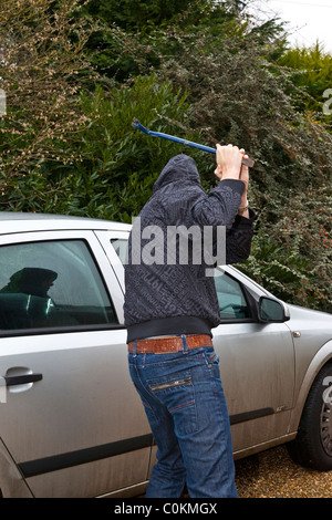 criminal breaking into a car - Stock Photo