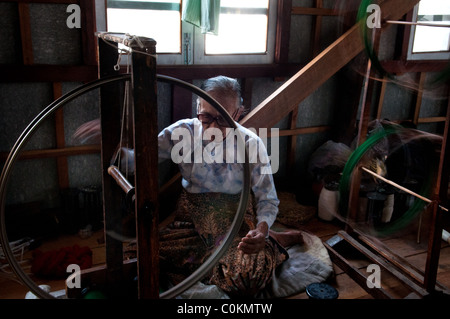 Elderly Intha lady using a  spinning wheel for silk - Stock Photo