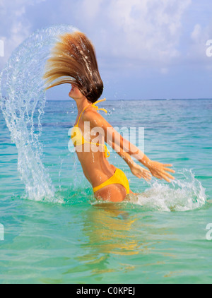 young woman in the ocean tossing her wet hair - Stock Photo