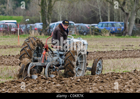 Farmer using a vintage tractor to plough a field - Stock Photo
