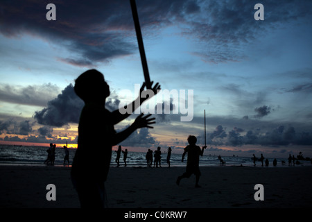 A beach scene at dusk as young children play balancing sticks at White Beach, Boracay Island, the Philippines. - Stock Photo