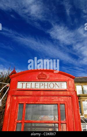 British red phone box against blue sky - Stock Photo
