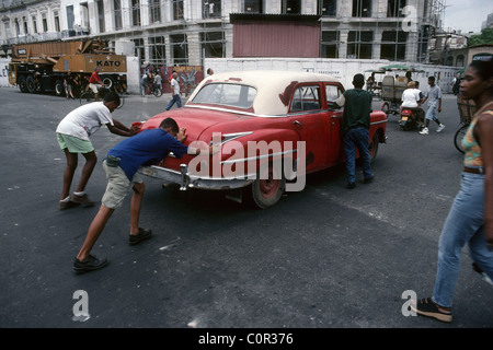 Havana. Cuba. Boys pushing a broken down old car in the streets of Centro Havana. - Stock Photo