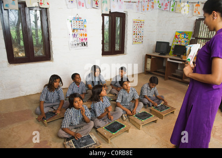 Woman teaching students in a classroom - Stock Photo
