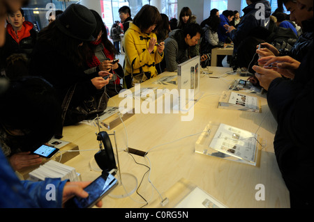 People trying out Apple iPhone 4 in the Apple Store in Beijing, China. 26-Feb-2011 - Stock Photo