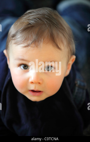 Baby boy, 10 month old, smiling friendly, at home. - Stock Photo