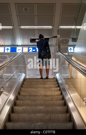 Person flight attendant on escalator steps in airport indoor, Fiumicino Rome Italy - Stock Photo