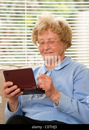 senior woman playing games with Nintendo DSi XL games console - Stock Photo