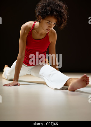 portrait of young adult latin american female doing yoga and stretching exercise in gym. - Stock Photo