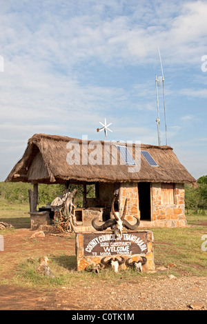 Solar panels & wind turbine on thatched roof game reserve office at entrance Masai Mara Kenya - Stock Photo