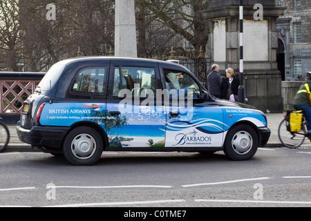 A famous London Black cab on Tower Bridge Advertising Barbados - Stock Photo