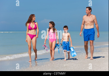 A happy family of mother, father and two children, son and daughter, in swimming costumes having fun in the sea - Stock Photo