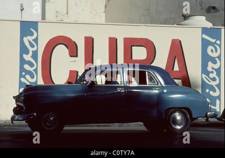 Havana. Cuba. Vintage American car in front of patriotic slogan 'Viva Cuba Libre' in Old Havana.