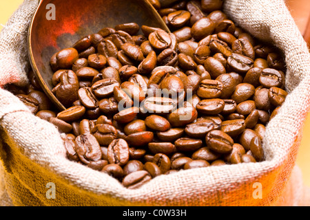 Sack of coffee beans and scoop. - Stock Photo