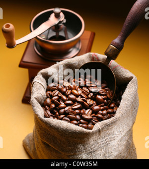 Sack of coffee beans and scoop. On a dark yellow background. - Stock Photo