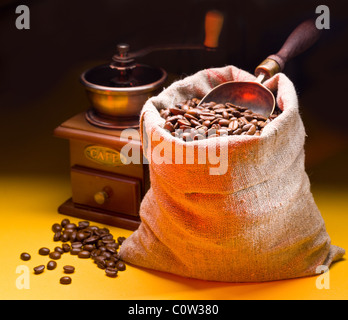 Sack of coffee beans and scoop. On a dark background. - Stock Photo