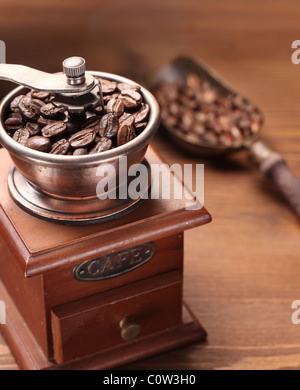 Roasted coffee beans are ground in a coffee grinder. - Stock Photo