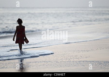 A young girl holding sandals in her right hand walks on the beach at sunset near Sao Filipe, Fogo Island, Cape Verde - Stock Photo