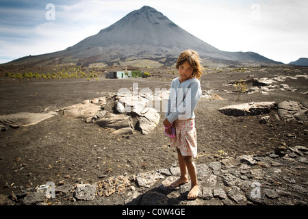 A girl stands barefoot on a paved road with Mount Fogo, and active volcano, in the background in Cha de Caldeiras, - Stock Photo