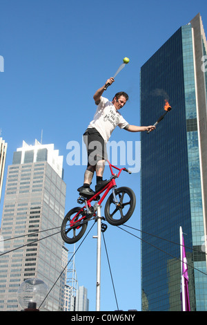 Street performer balancing his BMX bike on a tight rope whilst juggling fire torches, Sydney City, NSW, Australia. - Stock Photo