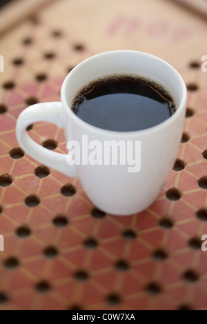 fresh coffee in white cup on game board - Stock Photo