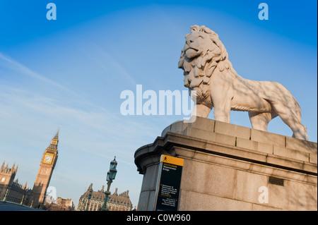 The South Bank Lion, at the south eastern end of Westminster Bridge, London, with  the Palace of Westminster in - Stock Photo