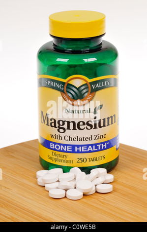 Bottle of Spring Valley Magnesium dietary supplement with tablets scattered. - Stock Photo