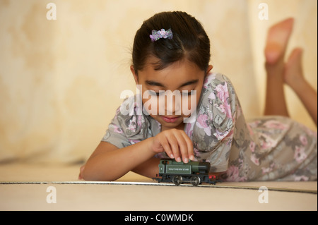 A young girl playing with her toy train set - Stock Photo