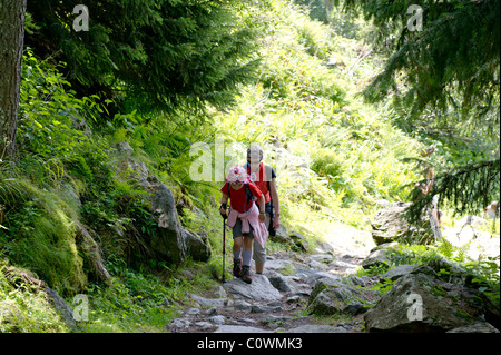 Mother and daughter walking along mountain path in the French Alps. - Stock Photo