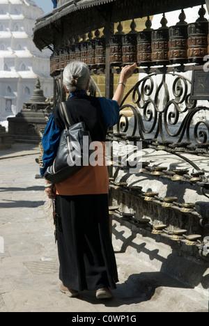 A woman turning prayer wheels at Swayambhunath, Kathmandu, Nepal. - Stock Photo